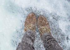 Pies femeninos en zapatos en el pavimento nevoso Imagen de archivo