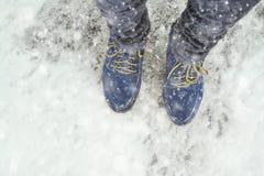 Pies femeninos en zapatos en el pavimento nevoso Foto de archivo