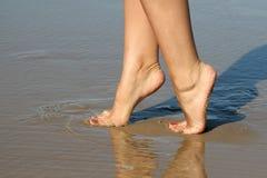 Pies femeninos hermosos en arena de mar Imágenes de archivo libres de regalías