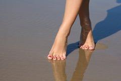 Pies femeninos hermosos en arena de mar Imagen de archivo