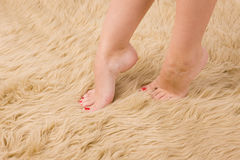 Pies femeninos hermosos en la alfombra de las lanas Fotografía de archivo libre de regalías