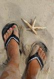 Pies femeninos hermosos en la playa Foto de archivo libre de regalías