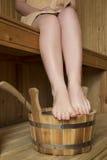 Pies femeninos hermosos en sauna, accesorios del baño Fotografía de archivo