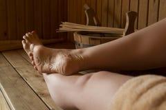 Pies femeninos hermosos en sauna, accesorios del baño Foto de archivo libre de regalías