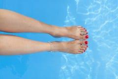 Pies femeninos que salpican en la piscina Fotos de archivo