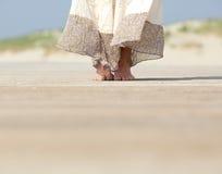 Pies femeninos que se colocan en la playa Imágenes de archivo libres de regalías