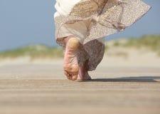 Pies femeninos que se van en la playa Imagen de archivo libre de regalías