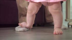 Pies infantiles que aprenden el paseo Concepto de la ayuda del padre Pequeños pasos en casa metrajes