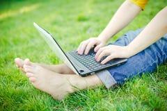 Pies jovenes de las muchachas del inconformista con el ordenador portátil en un parque Imagen de archivo
