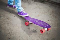 Pies jovenes del skater en gumshoes y vaqueros Foto de archivo libre de regalías