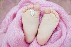 Pies lindos del ` s del bebé cubiertos en el abrigo rosado imagen de archivo