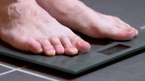 Pies masculinos en las escalas de cristal, la dieta de los hombres, peso corporal almacen de metraje de vídeo