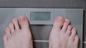 Pies masculinos en las escalas de cristal, la dieta de los hombres, peso corporal metrajes