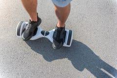 Pies masculinos que van en hoverboard en la calle Fotografía de archivo libre de regalías