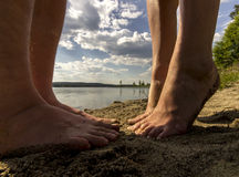 Pies masculinos y femeninos en arena Foto de archivo libre de regalías