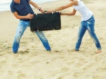 Pies masculinos y femeninos en la arena cerca del mar con una maleta de cuero Imagen de archivo libre de regalías