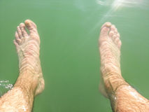 Pies mojados del hombre debajo del agua Foto de archivo libre de regalías