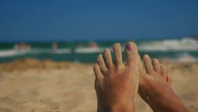 Pies perezosos en la playa con la arena en los dedos del pie almacen de metraje de vídeo