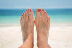 Pies, playa y mar arenosos desnudos de la mujer Imagen de archivo