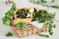 Pies of puff pastry with parsley, dill, green onions in basket Stock Photos