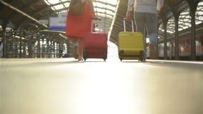 Pies que caminan en los pasajeros de la plataforma con una maleta Pares jovenes que caminan a lo largo de la plataforma al tren c almacen de video