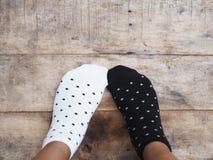 Pies que llevan calcetines blancos y negros del lunar imagen de archivo