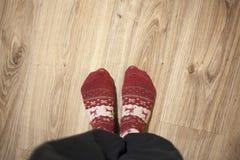Pies que llevan calcetines de la Navidad en el piso de madera Familia feliz en el país Concepto de los días de fiesta de Navidad foto de archivo libre de regalías