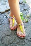 Pies que llevan las sandalias del verano Imágenes de archivo libres de regalías