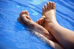 Pies que se baten en agua clara de la piscina. Imagenes de archivo
