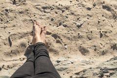 Pies relajados en la arena de la playa imagen de archivo