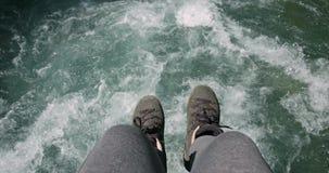 Pies sobre el río del agua que se sienta en concepto de la forma de vida del viaje del borde del puente metrajes