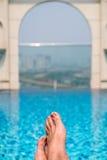 Pies sobre la piscina chispeante encima del edificio con el aeri de Saigon Foto de archivo