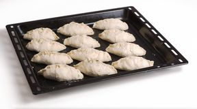Pies ready for baking lying on a black steel baking sheet. Three Stock Photos