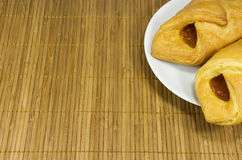 Pies on a white plate. Two pies on the white plate standing on a bamboo napkin Royalty Free Stock Image