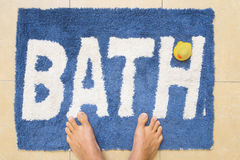 Pies y Duckie en alfombra de baño imagen de archivo libre de regalías
