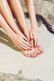 Pies y manos bonitos de la mujer con la manicura roja Fotos de archivo