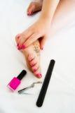 Pies y manos con el fucsia del esmalte de uñas Fotografía de archivo