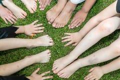Pies y manos de niños en el césped Imagen de archivo libre de regalías