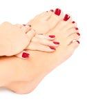 Pies y manos femeninos con la manicura roja Fotos de archivo