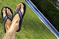 Pies y sandalias por la piscina Foto de archivo libre de regalías
