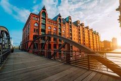 Pieszy łuku most nad kanałami w Speicherstadt Hamburg Grże złotego godzina zmierzchu światło na czerwonych cegłach obraz stock