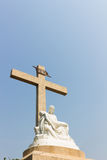 Pieta statue with cross and sky background. A statue with Pieta style and cross+sky background Royalty Free Stock Image