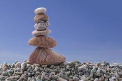 Pietra dell'equilibrio sulla roccia del mucchio con il fondo del cielo blu Fotografia Stock
