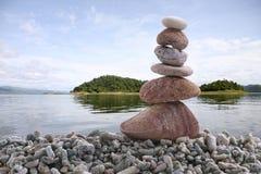 Pietra dell'equilibrio sulla roccia del mucchio con il fondo del fiume Fotografia Stock Libera da Diritti