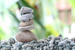Pietra dell'equilibrio sulla roccia del mucchio con il fondo del giardino Fotografia Stock