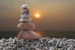 Pietra dell'equilibrio sulla roccia del mucchio con il fondo del mare di tramonto Fotografie Stock Libere da Diritti