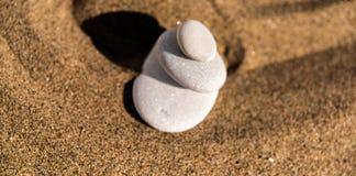 Pietra di meditazione di zen in sabbia, nel concetto per armonia di purezza e in spi fotografie stock