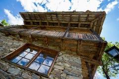 Pietra di riflessioni della nuvola della finestra vecchia e casa di legno fotografia stock