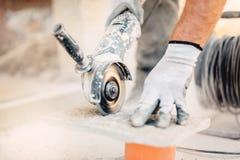 Pietra di taglio del lavoratore con la smerigliatrice Spolveri mentre pavimentazione della macina fotografia stock libera da diritti