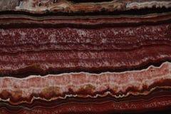 Pietra naturale dell'onyx di colore rosso con le striscie scure e palide e un bello modello fotografia stock libera da diritti